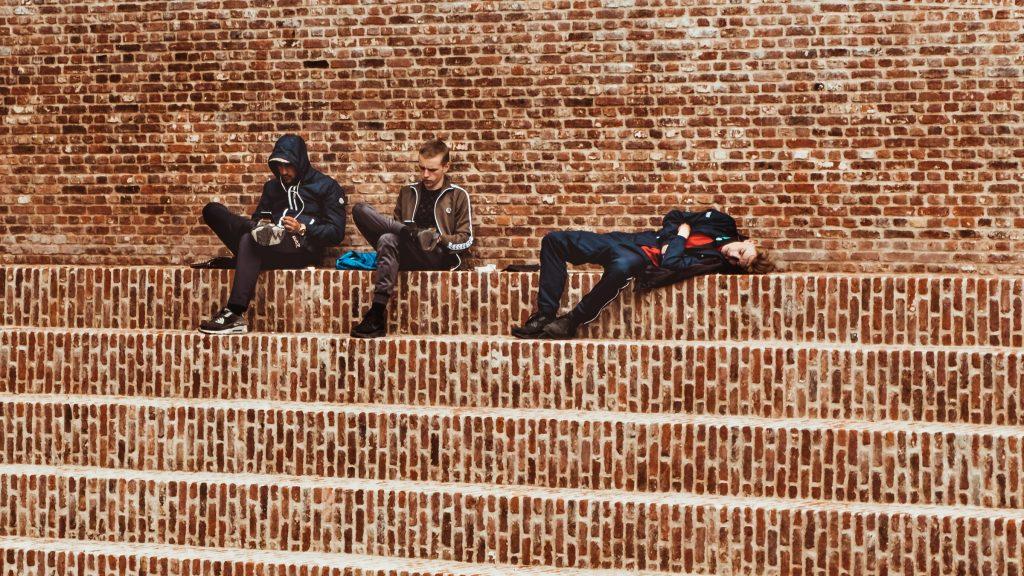 punaisenruskealla tiiliportaikolla istuu ja makoilee kolme nuorta miestä