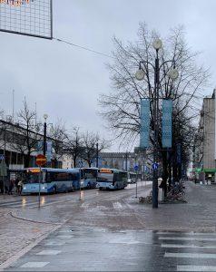 Lahden sateista kaupunkimaisemaa, jossa on muutama bussi ja katupuita.