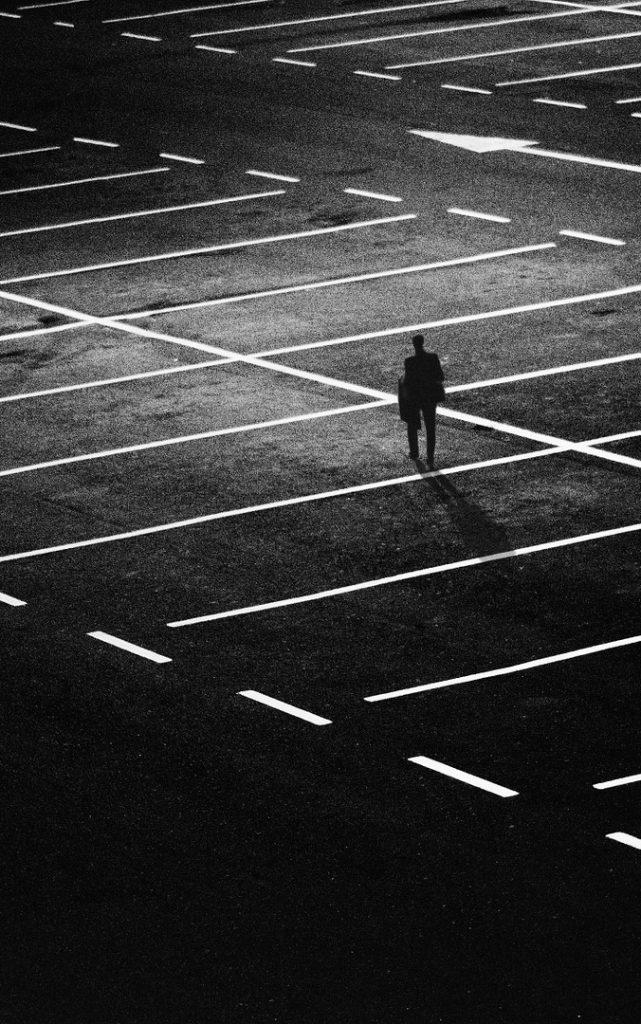 Mustavalkoinen kuva, jossa henkilö kävelee yksin tyhjällä parkkipaikalla