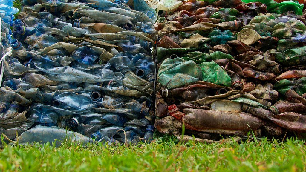 kaksi paalutettua kasaa muovipulloja nurmikolla