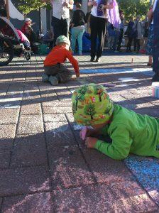 Lapset piirtämässä katuliiduilla